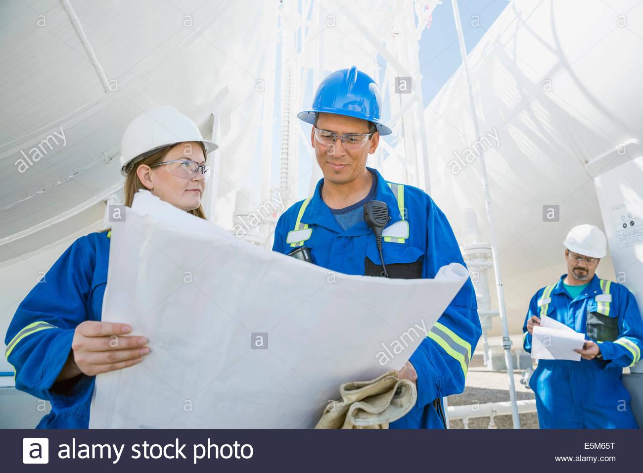 Workers blueprints à l'usine à gaz Photo Stock