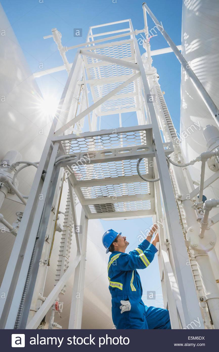 Travailleur de l'usine à gaz à l'échelle d'escalade Photo Stock