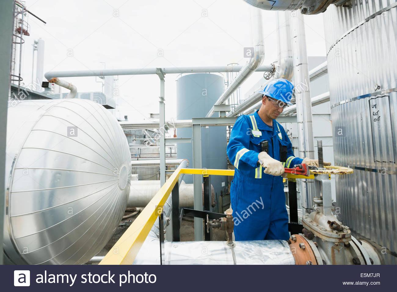 Travailleur à l'aide d'une clé à pipe à l'usine à gaz Photo Stock