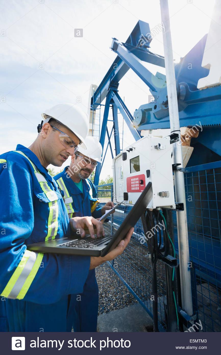 Les travailleurs de sexe masculin avec ordinateur portable à bien d'huile Photo Stock