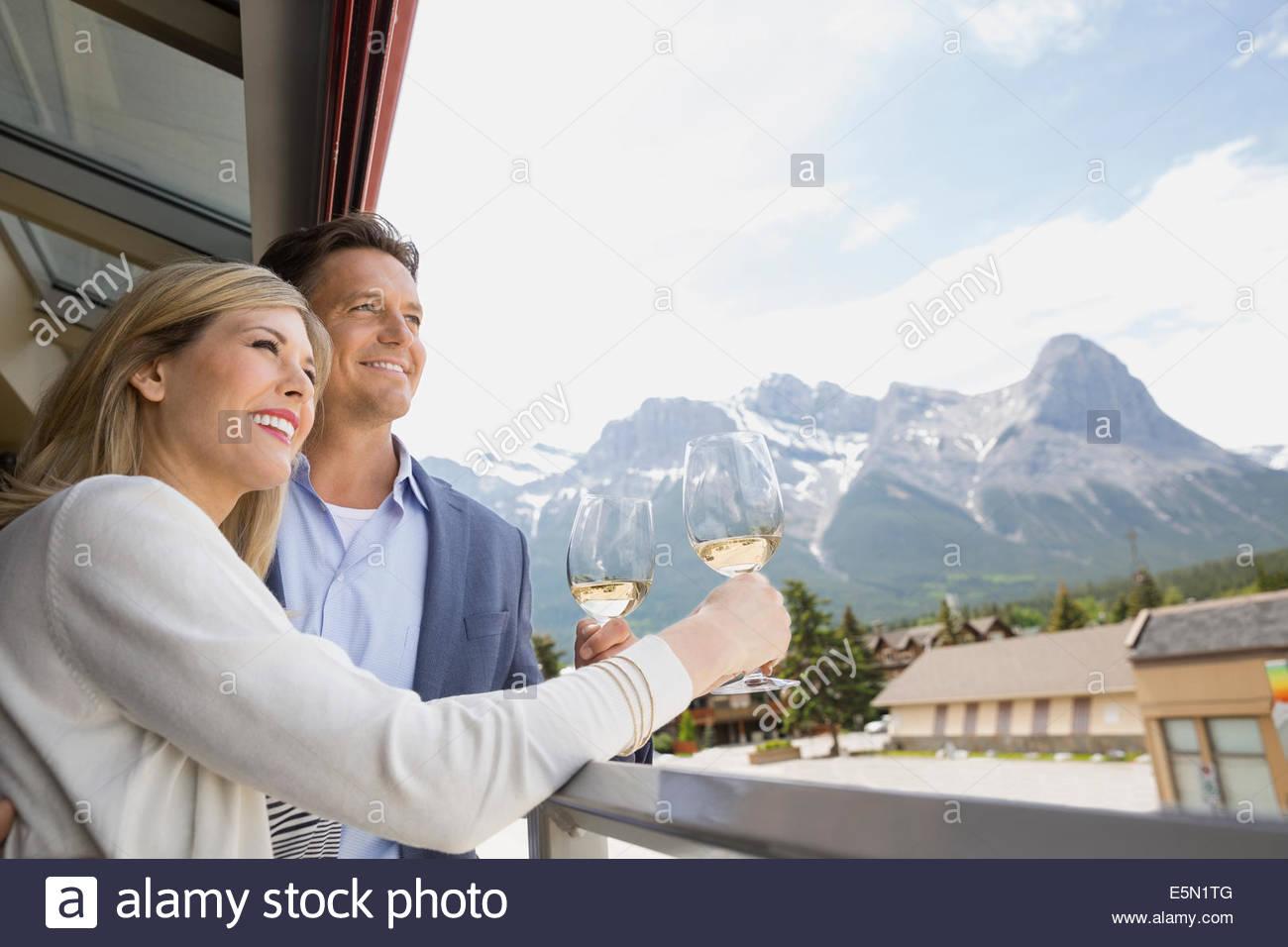 Couple drinking wine sur balcon avec vue sur la montagne Photo Stock