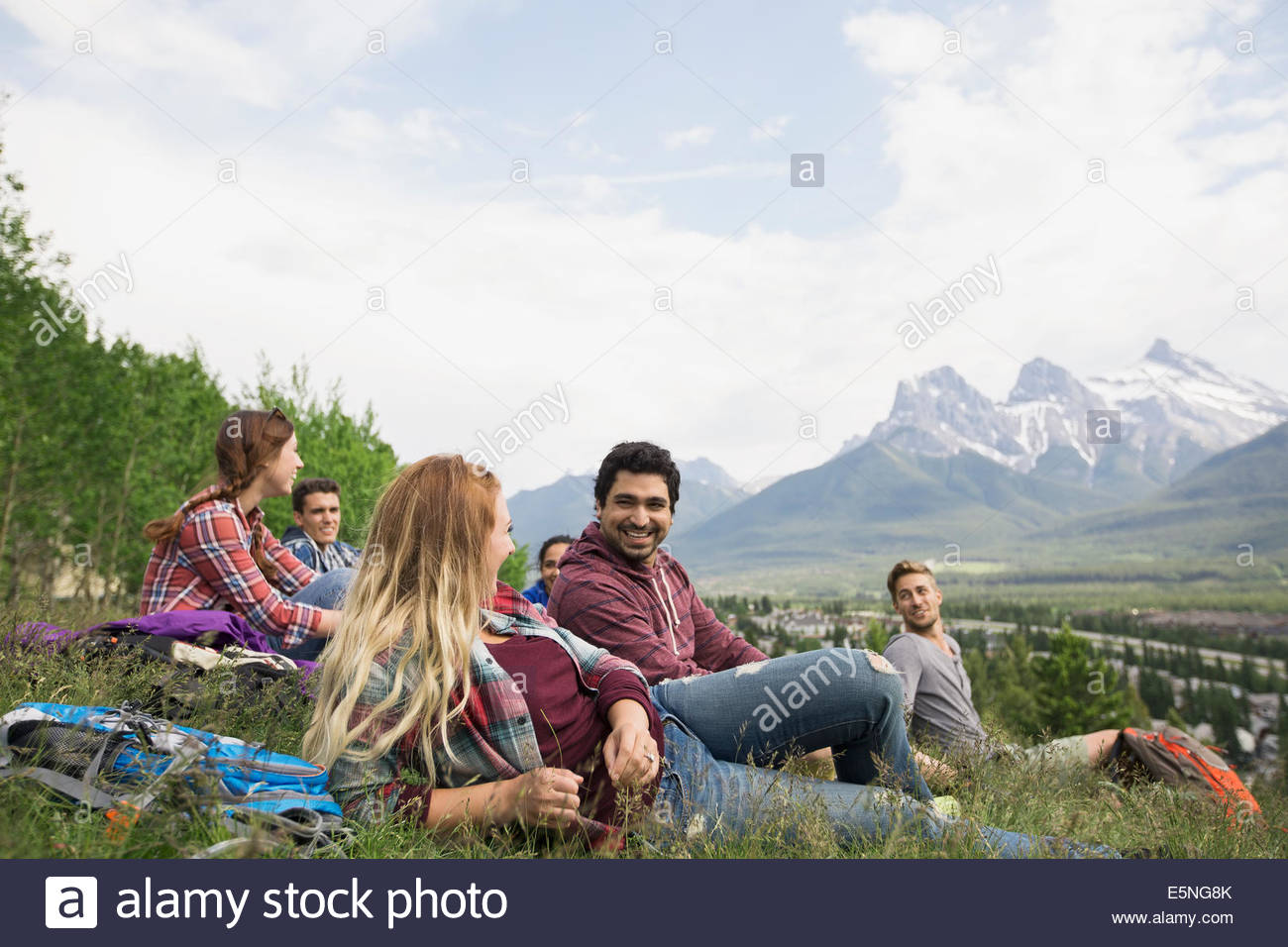 Les amis se détendre dans l'herbe près des montagnes Photo Stock