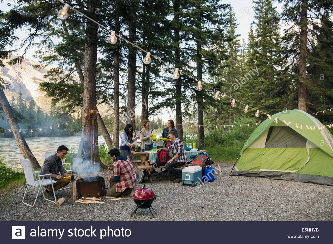 Friends hanging out at lakeside camping Photo Stock