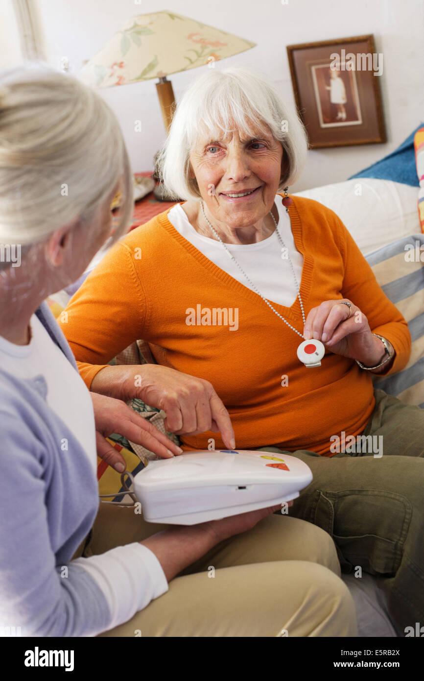 Bouton d'appel d'urgence, personnes âgées femme portant une unité d'assistance à Photo Stock