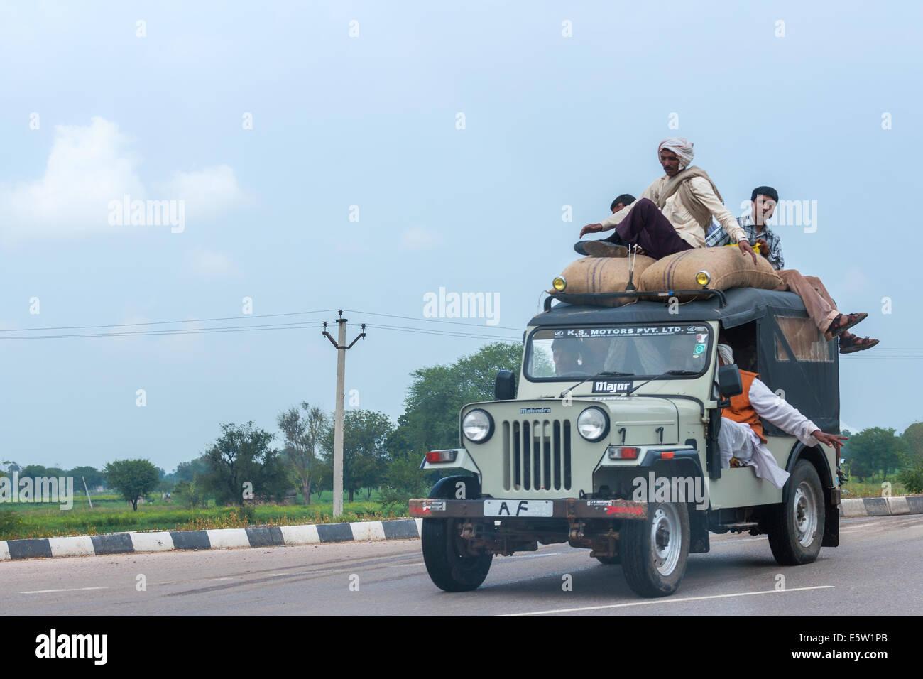 Jeep surchargée avec des sacs et des personnes sur le toit de la conduite sur route. Photo Stock