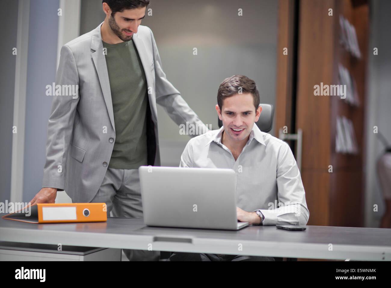 Deux hommes dans un bureau, à l'aide d'ordinateur portable Photo Stock