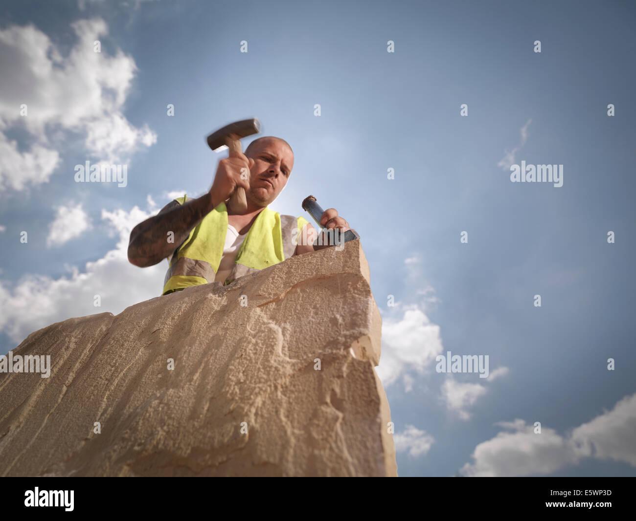 Ouvrier carrier de grès fractionnement dans le Yorkshire carrière de pierres Photo Stock