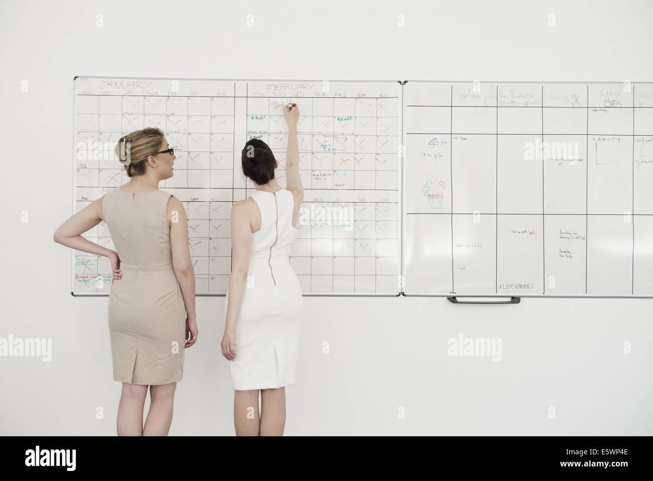 Deux jeunes sur la planification d affaires tableau blanc bureau