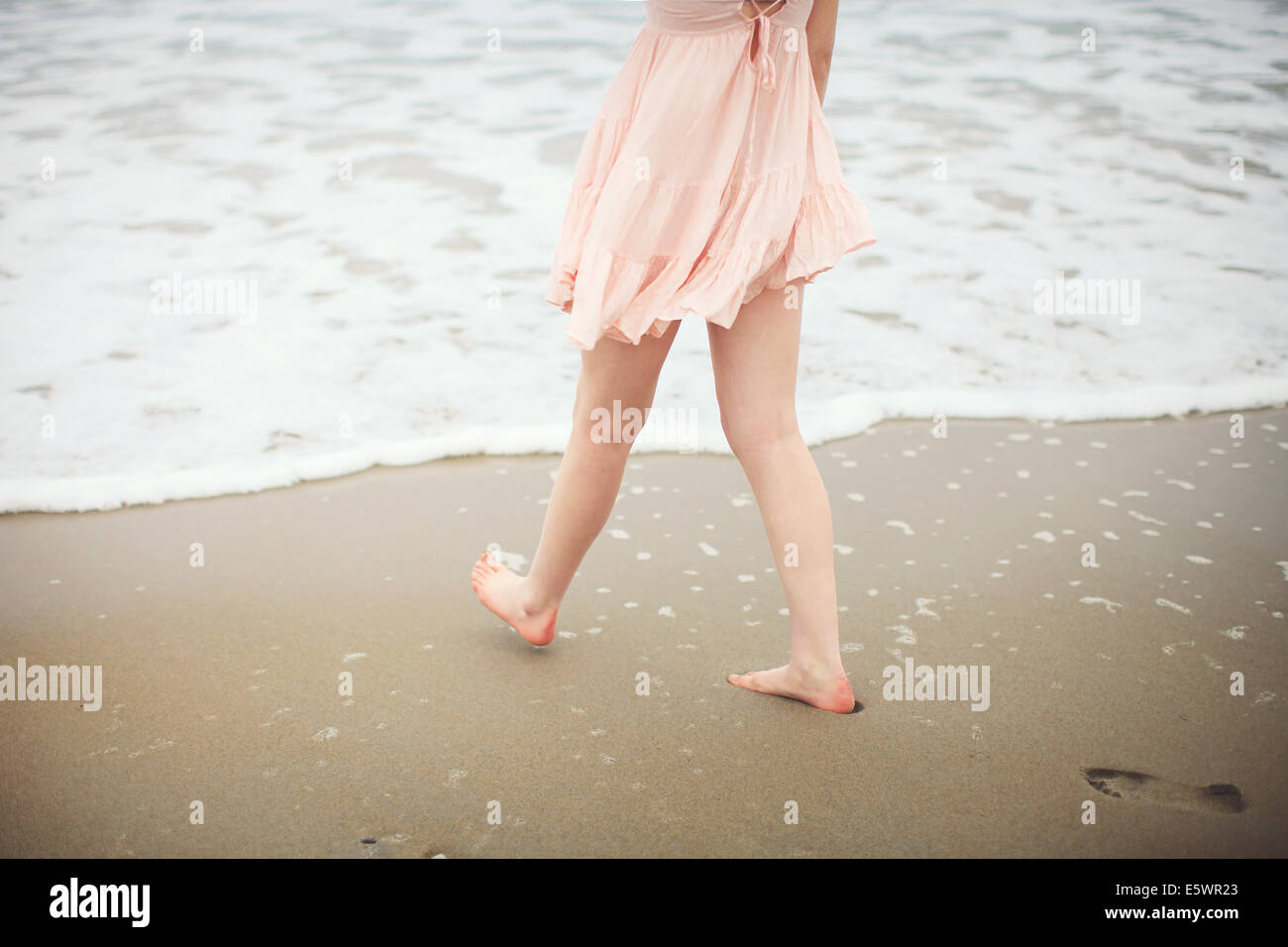 Cropped shot of woman paddling on beach Photo Stock