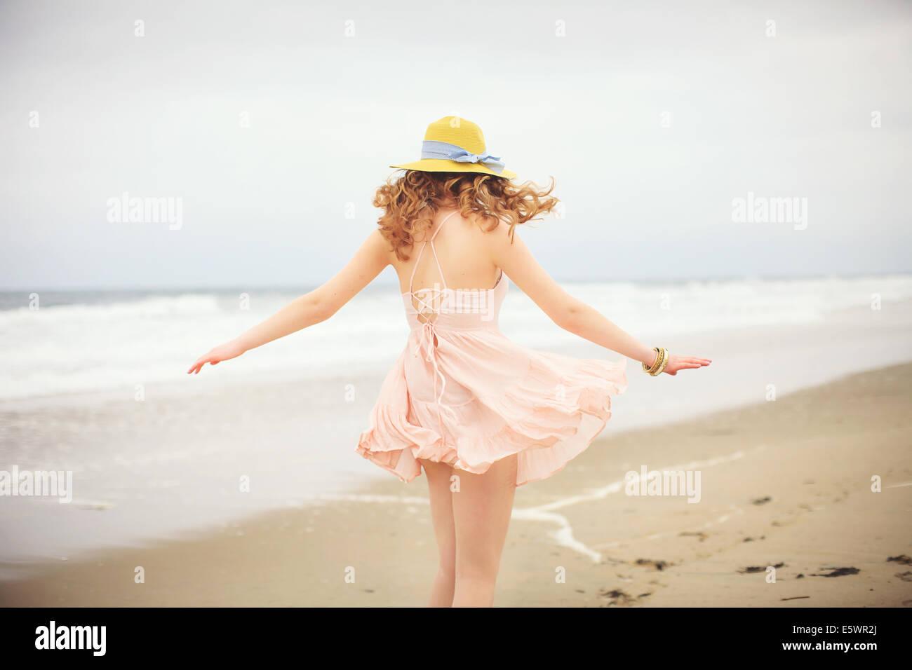 Vue arrière de l'adolescente se promener sur la plage, l'établissement Hampton, New Hampshire, Photo Stock