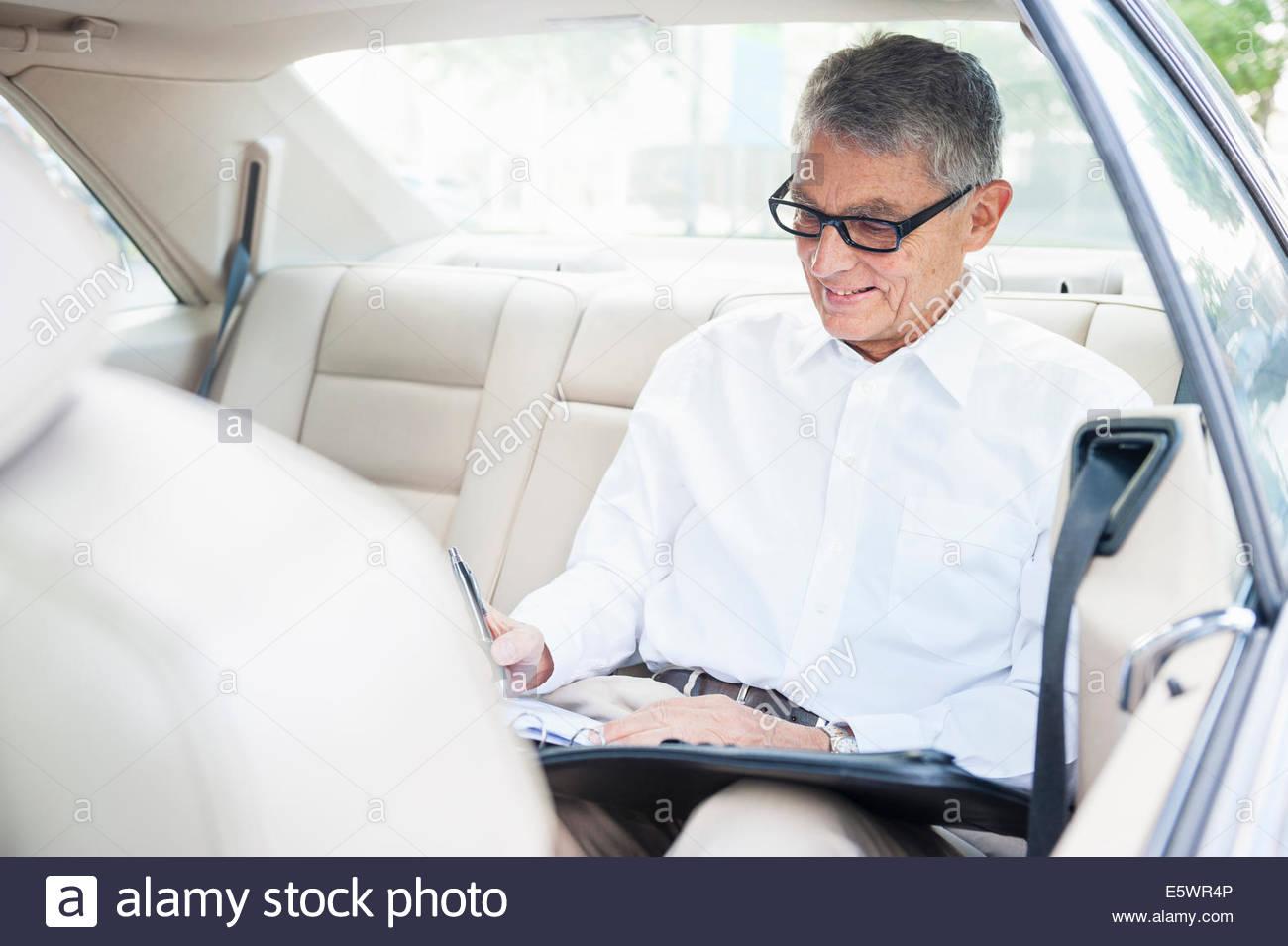 Senior adult businessman siège arrière de voiture, prendre des notes Photo Stock