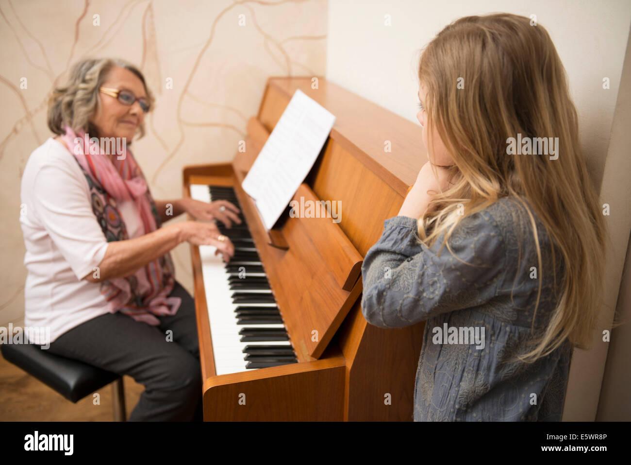 Petite-fille regardant grand-mère joue du piano Photo Stock