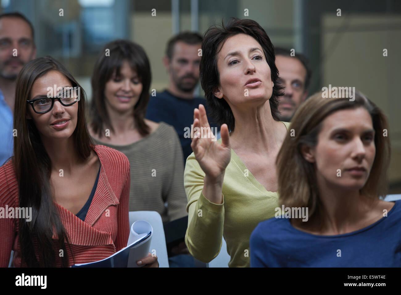 Regarder la présentation de groupe, woman raising hand Photo Stock