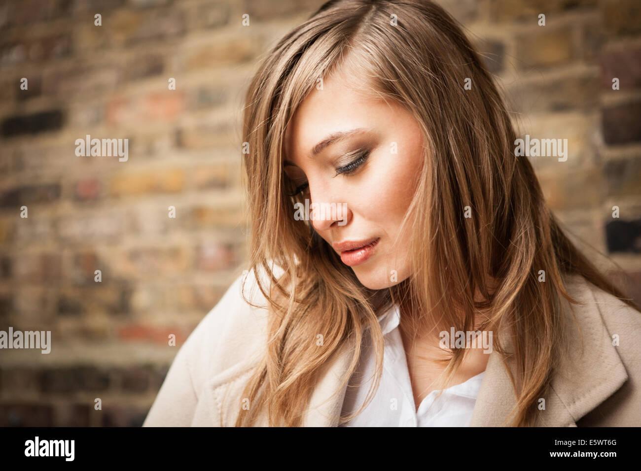 Femme avec les yeux baissés, mur de brique en arrière-plan Photo Stock