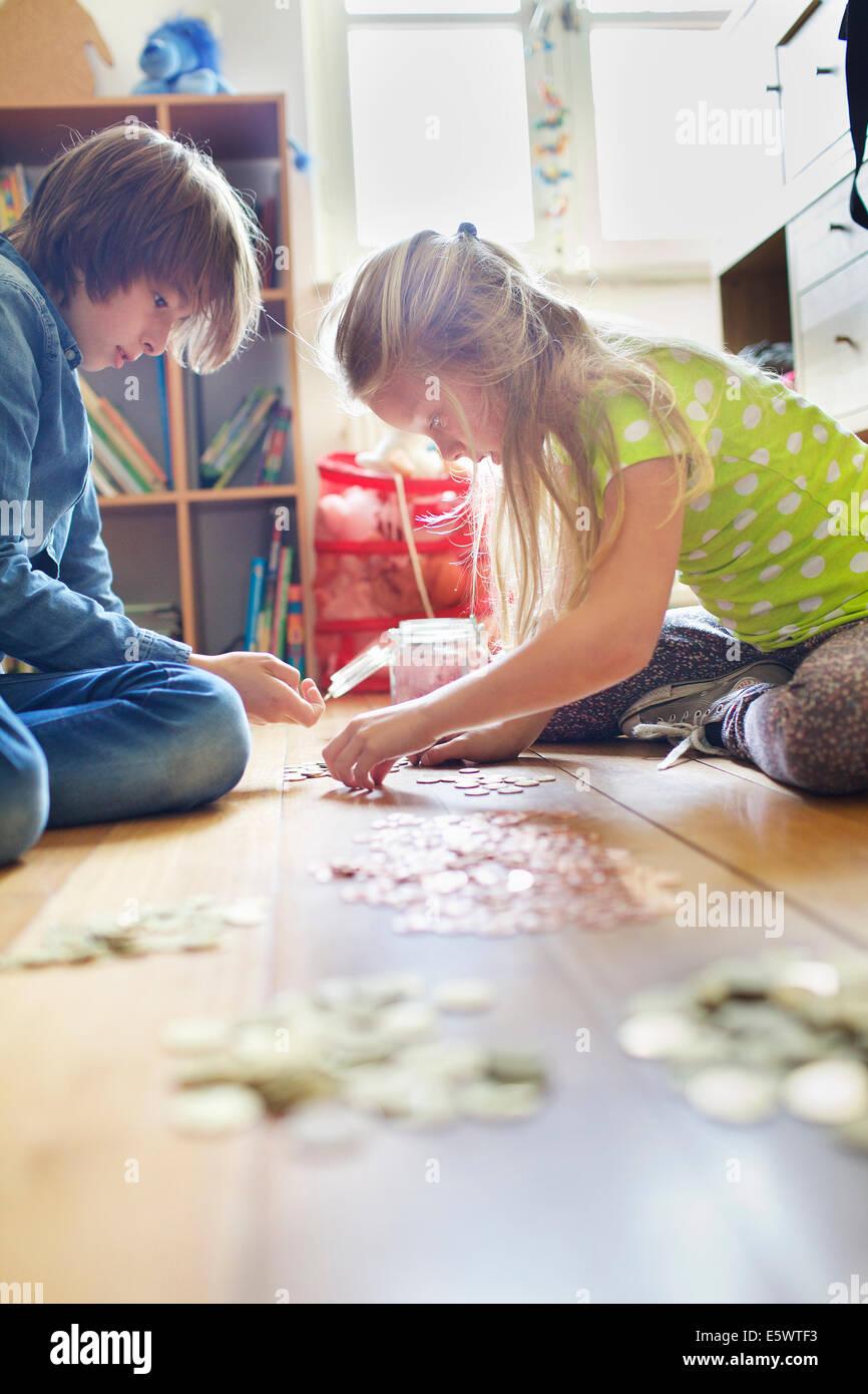 Frère et sœur à compter des pièces de savings jar Photo Stock