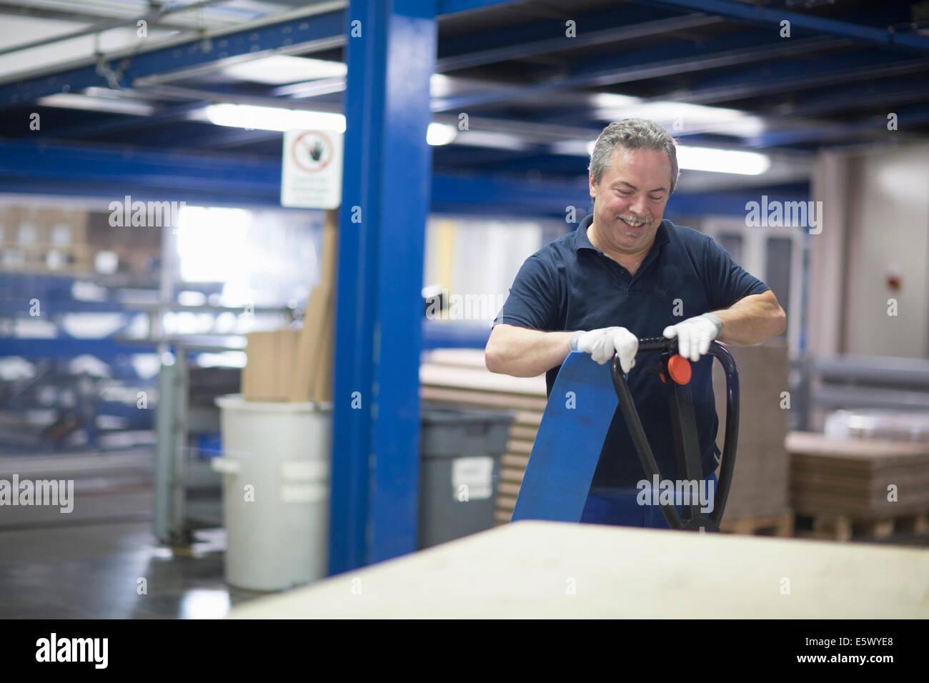 Hauts employé d'usine à l'aide de transpalette Photo Stock