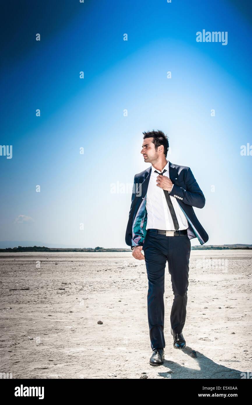Jeune homme marcher à travers désert paysage seul Photo Stock