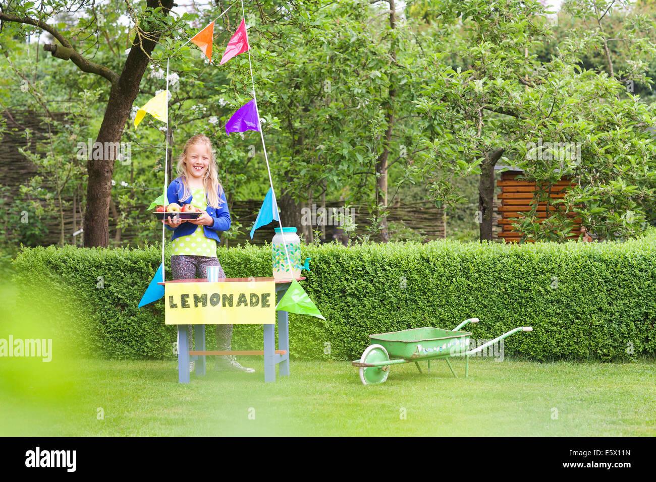 Lemonade stand girl avec bac de pommes derrière son stand Photo Stock