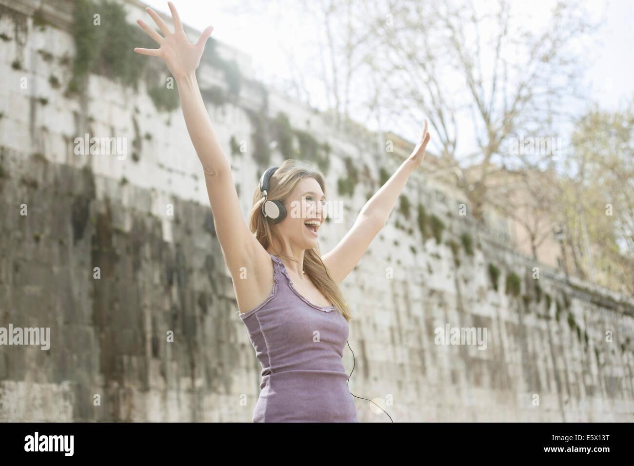Happy young woman, portant des écouteurs et raising arms Photo Stock