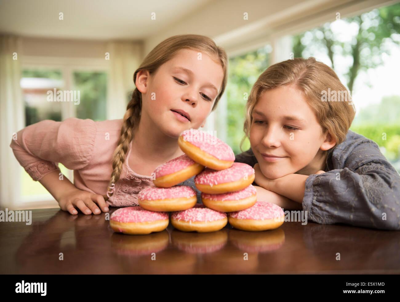 Deux soeurs à contempler avec pile de trous de beignes sur compteur de cuisine Photo Stock