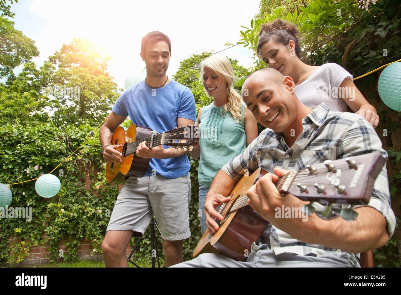 Les amis masculins playing acoustic guitar dans le jardin pour les amies Photo Stock