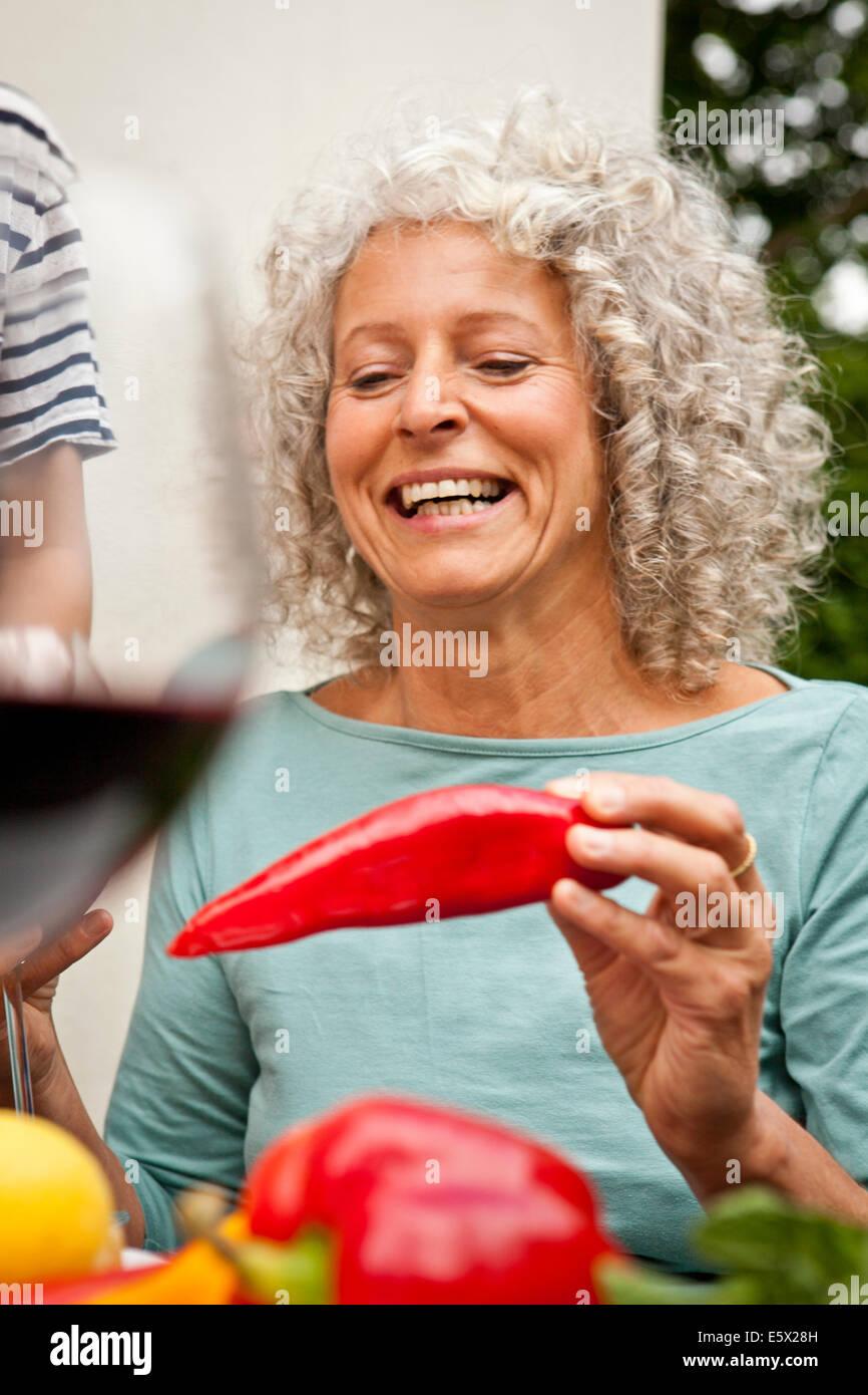 Mature Woman holding un poivron rouge Photo Stock