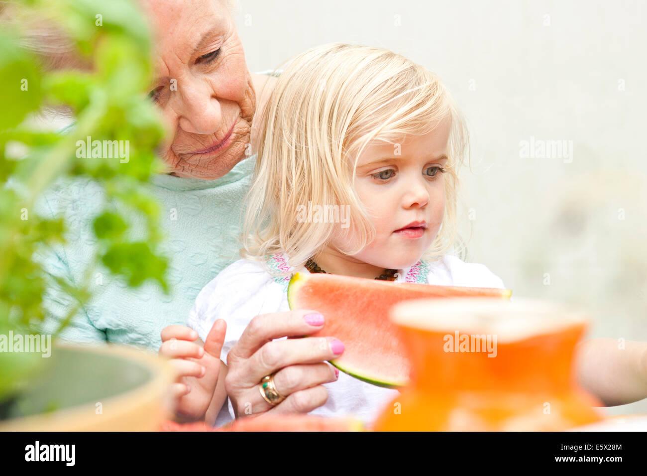 Hauts femme et enfant en arrière-petite-fille manger melon tranche à table de jardin Photo Stock