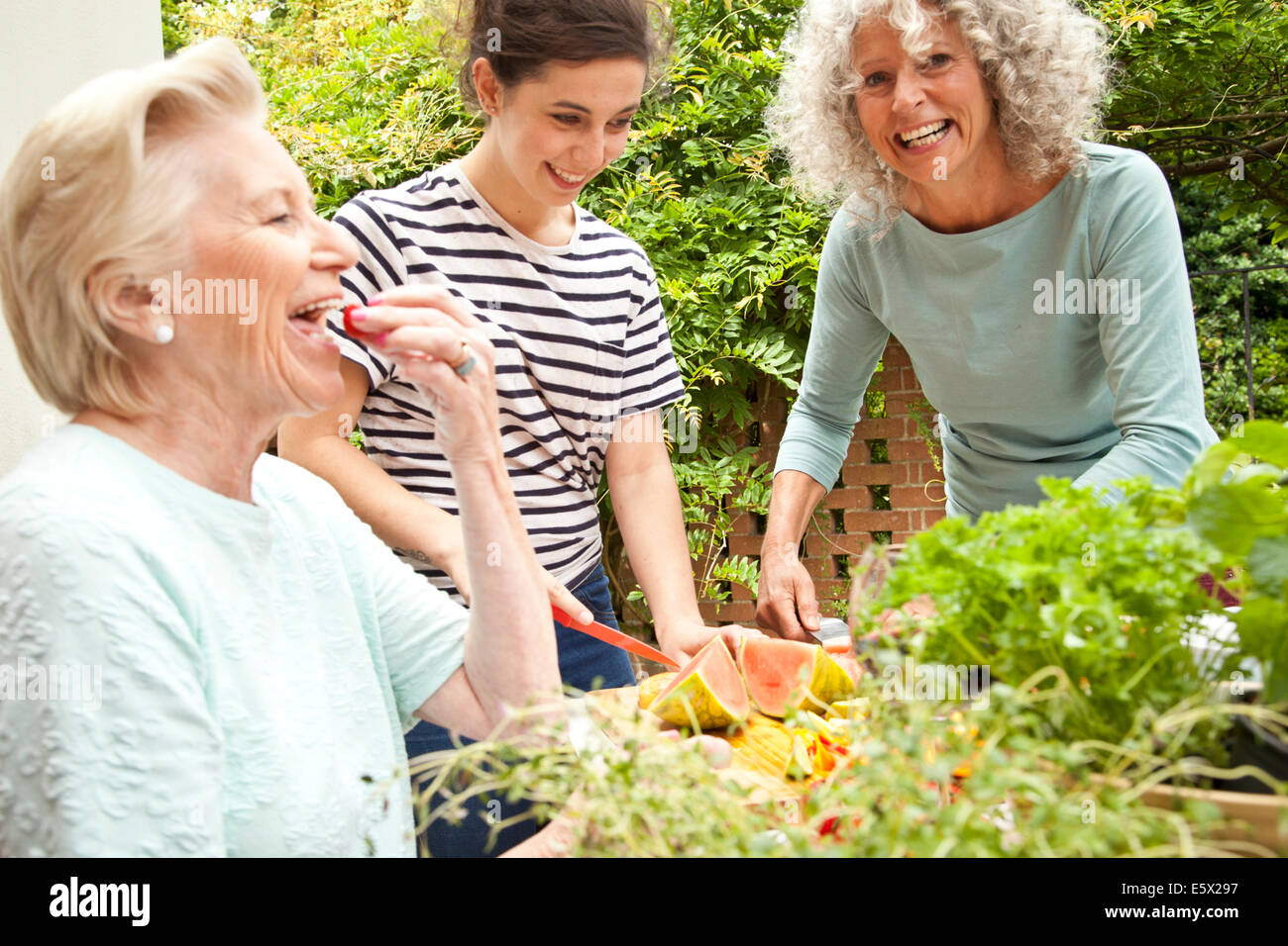 Trois femmes de préparer des aliments à table de jardin Photo Stock