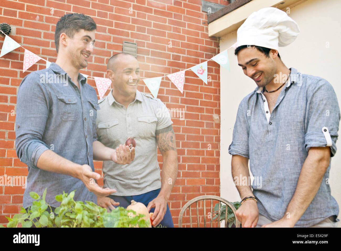 Amis de rire de chapeau de chef tout en préparant la nourriture pour jardin barbecue Photo Stock