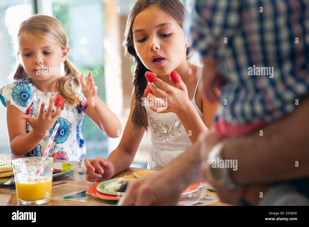Deux soeurs avec framboises sur leurs doigts au bar de petit-déjeuner cuisine Photo Stock