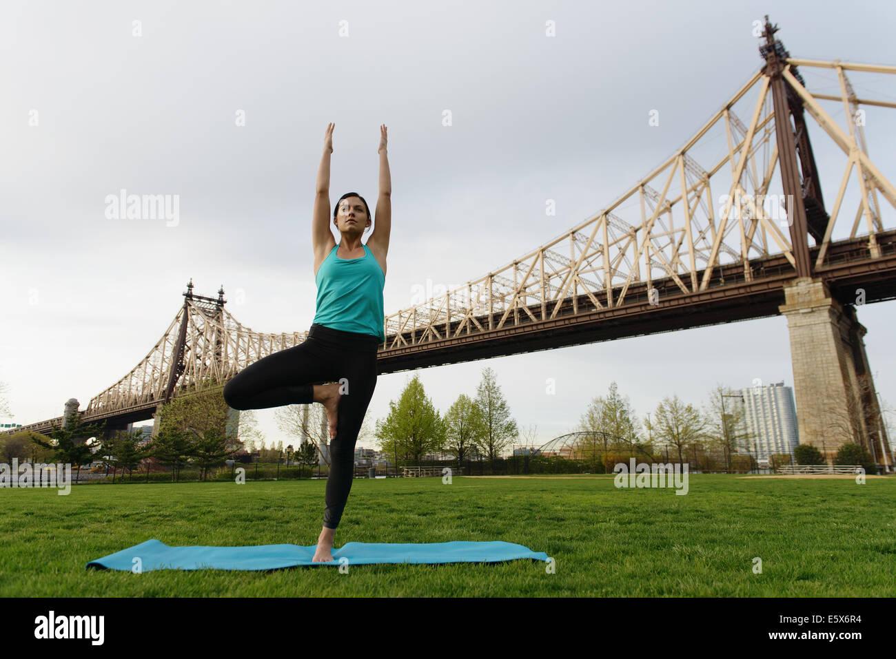 Young woman practicing yoga posture de l'arbre dans le parc de la ville Banque D'Images
