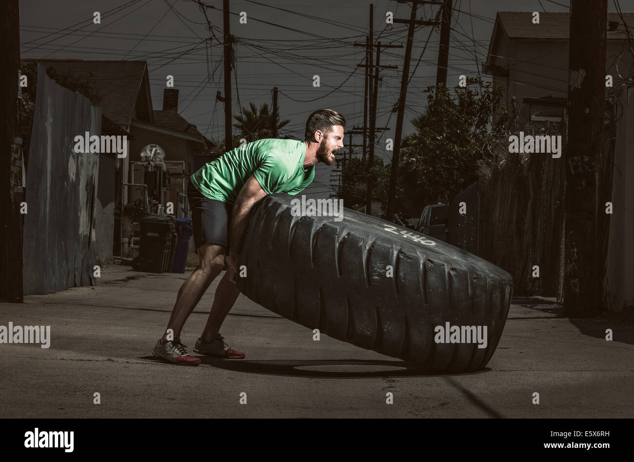 Young adult man lifting des pneus Photo Stock