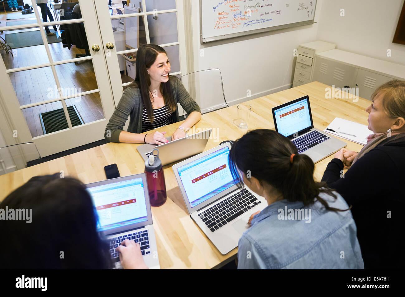 Collègues de sexe féminin dans une réunion avec des ordinateurs portables Photo Stock