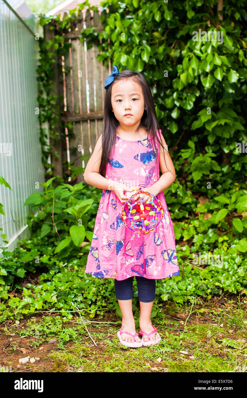 Portrait of young girl in garden with toy Photo Stock
