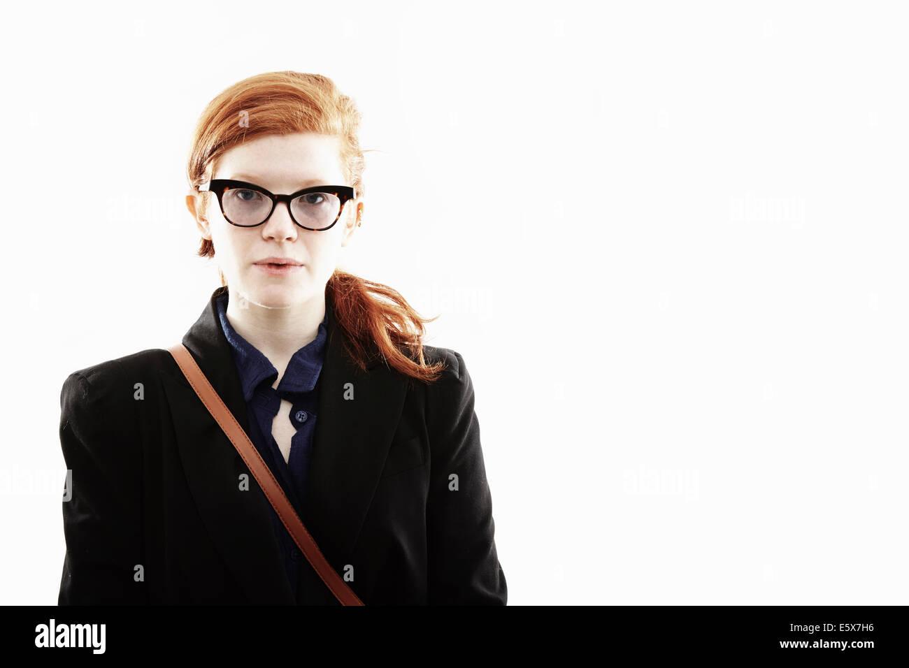 Studio portrait de jeune femme avec des lunettes et expression vide Photo Stock
