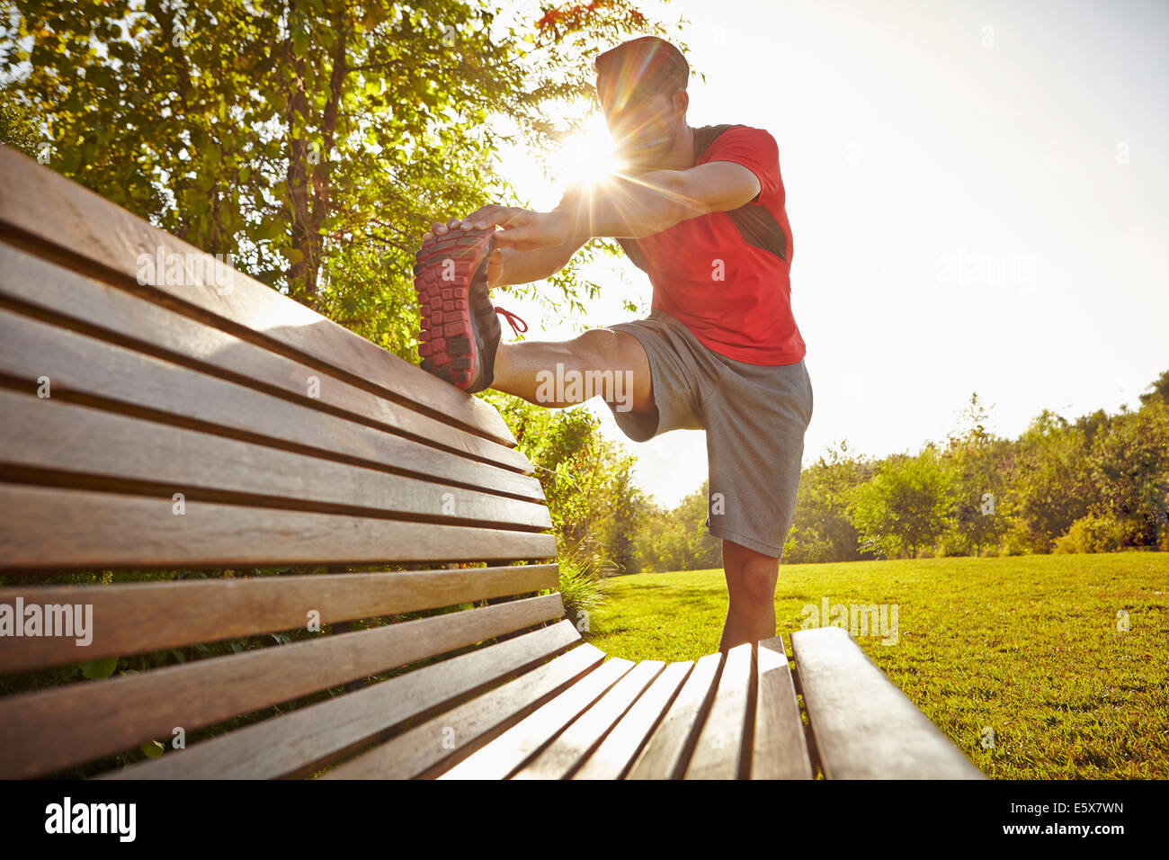 Young male runner stretching jambes sur banc de parc Photo Stock