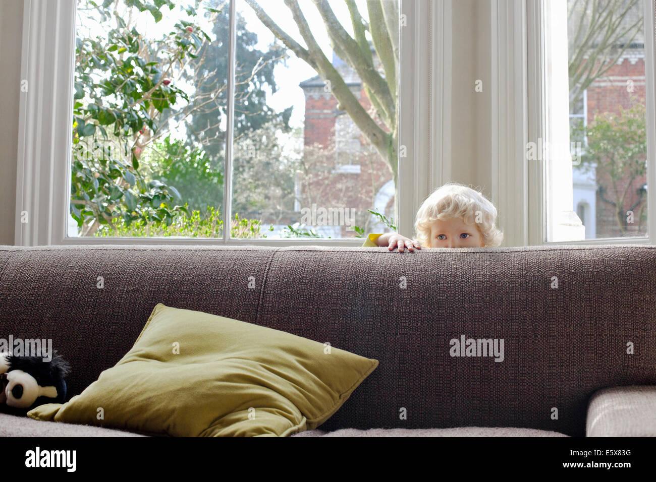 Portrait of cute blonde mâles tout-petit se cacher derrière un canapé Photo Stock
