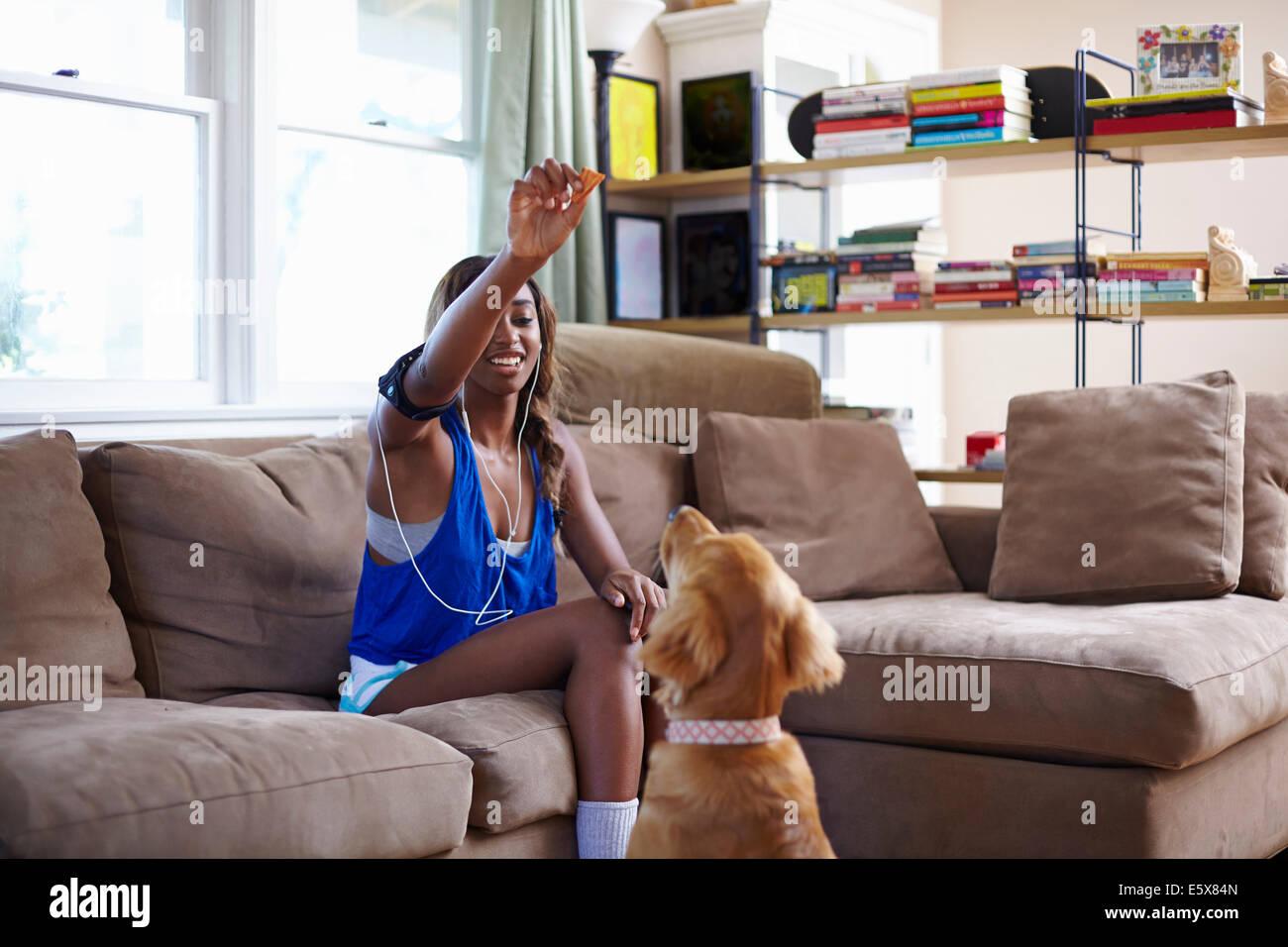 Jeune Femme prenant une pause formation, holding up biscuit pour chien dans la salle de séjour Photo Stock