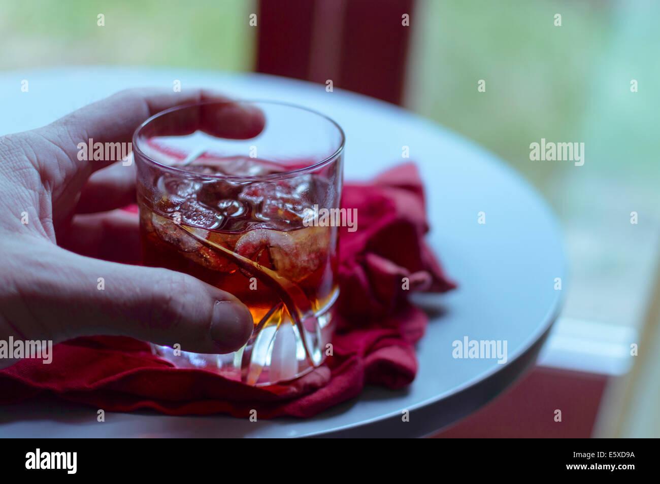 Un verre d'amaretto avec de la glace tenu par une main Banque D'Images
