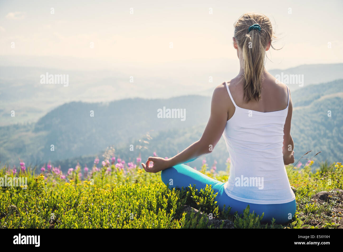 Jeune femme méditer sur le sommet de la montagne Photo Stock