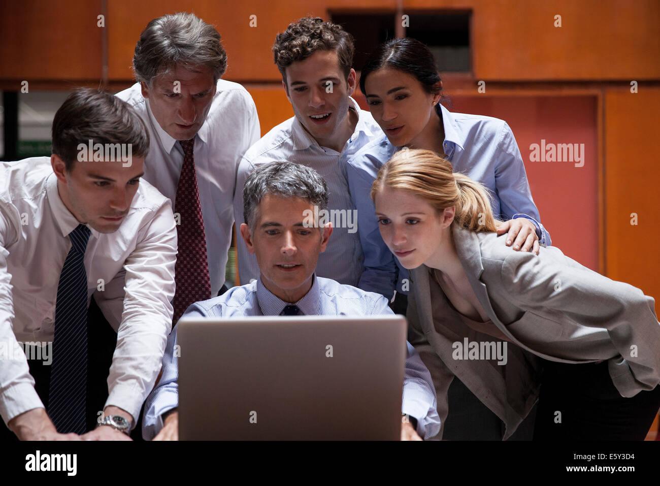 Des collègues de foule autour de collègue regardant par-dessus son épaule at laptop computer Photo Stock