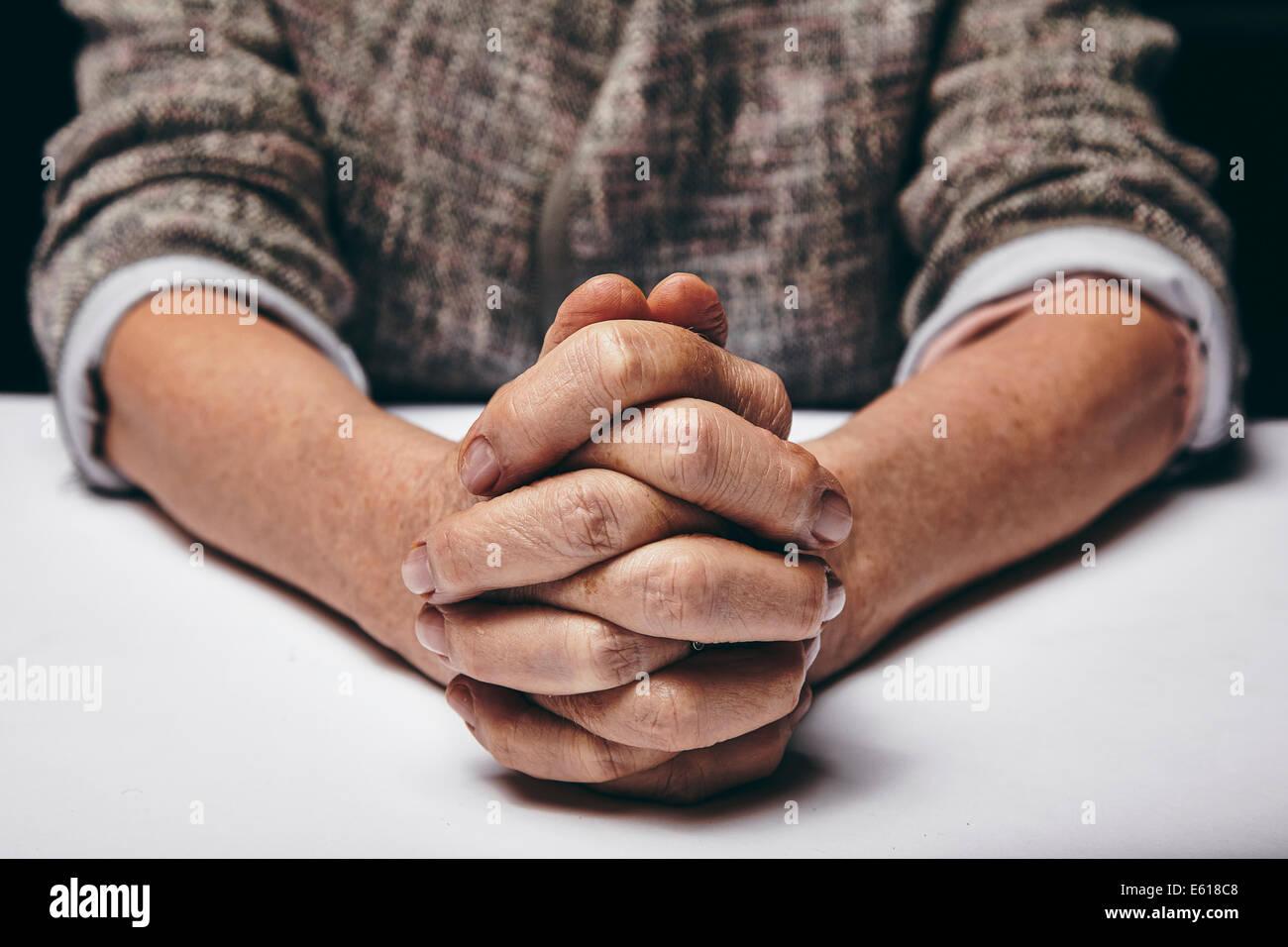 La photographie de studio priant mains d'une femme senior sur table. Vieux les mains jointes sur une table. Photo Stock
