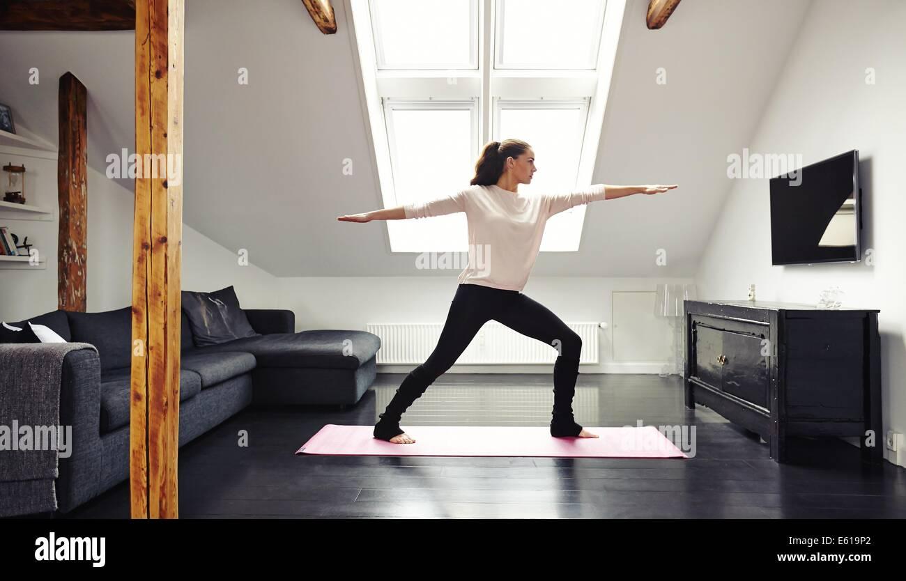Longueur totale de l'image attractive young woman exercising on mat dans la salle de séjour. Fit dame faisant du Banque D'Images