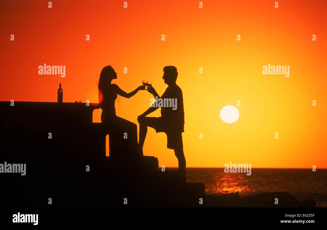Couple toasting with la vie et l'amour au coucher du soleil l'Uruguay Photo Stock
