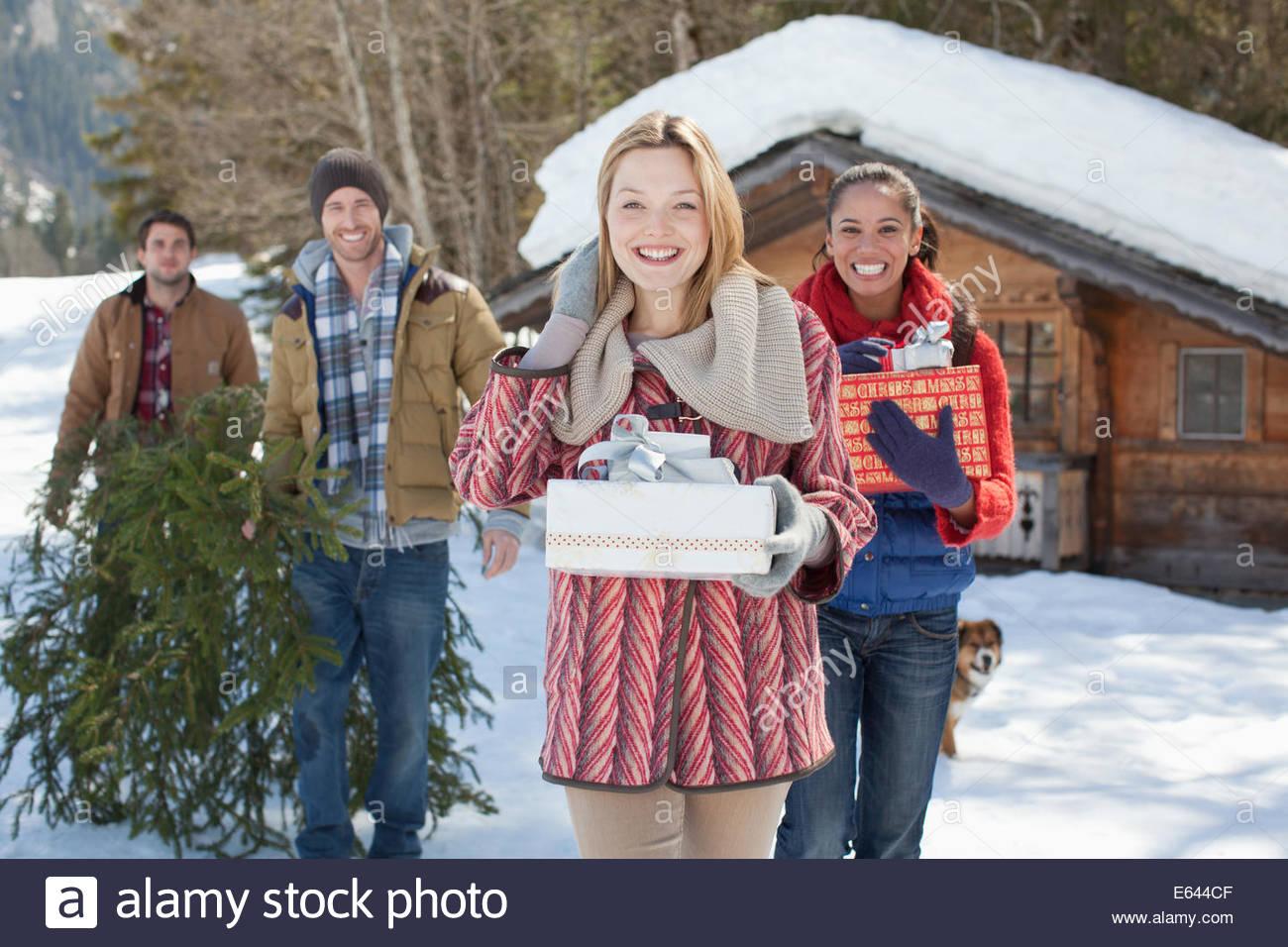Portrait of smiling couples avec des cadeaux et de l'arbre de Noël dans la neige Photo Stock