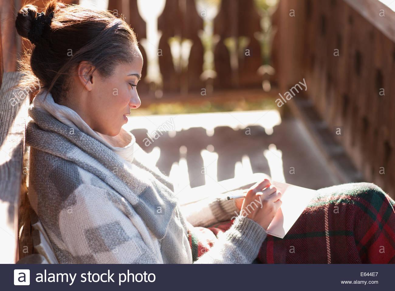 Femme souriante avec stylo et papier sur cabin porch Photo Stock