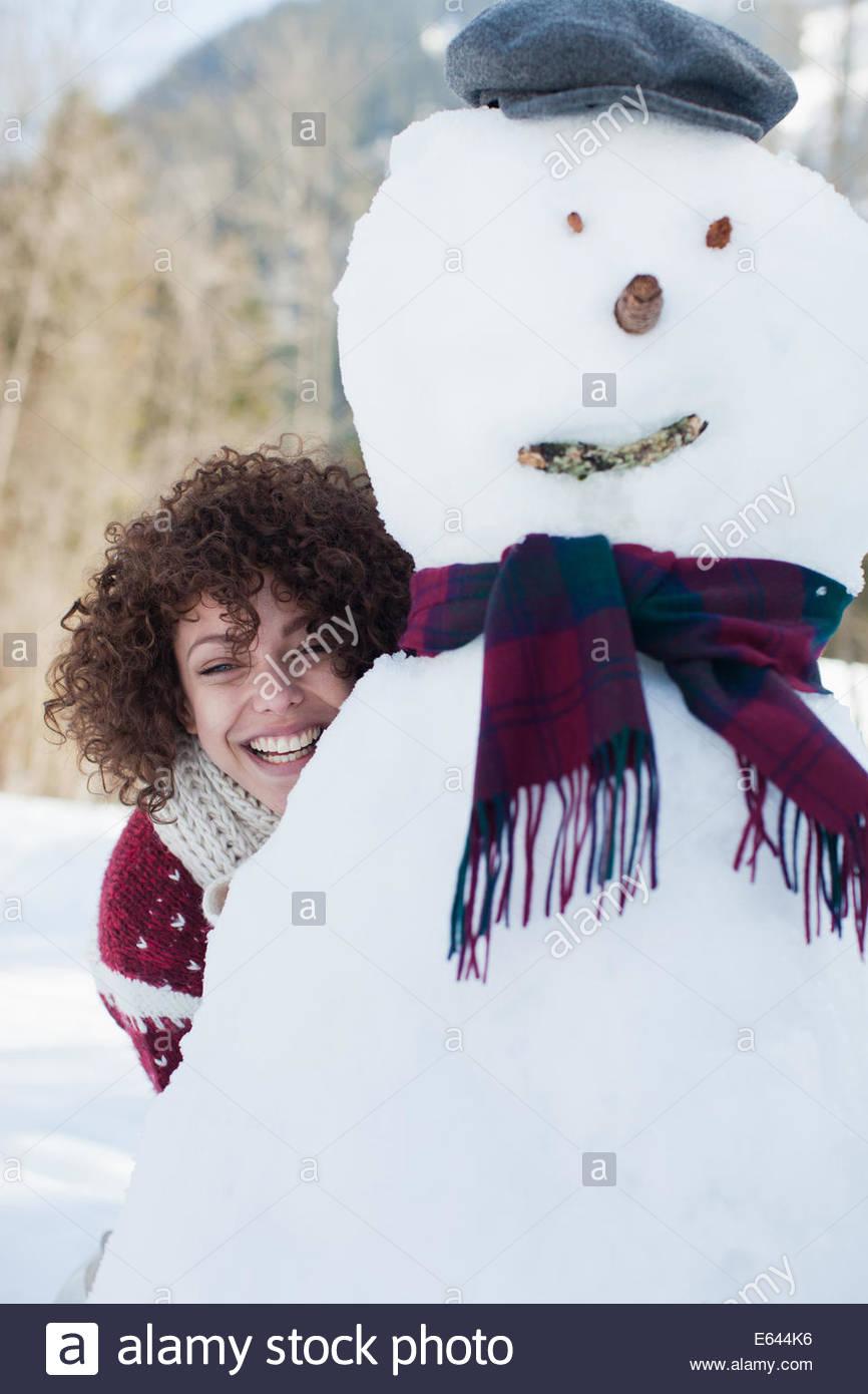 Femme de se cacher derrière le Snowman Photo Stock