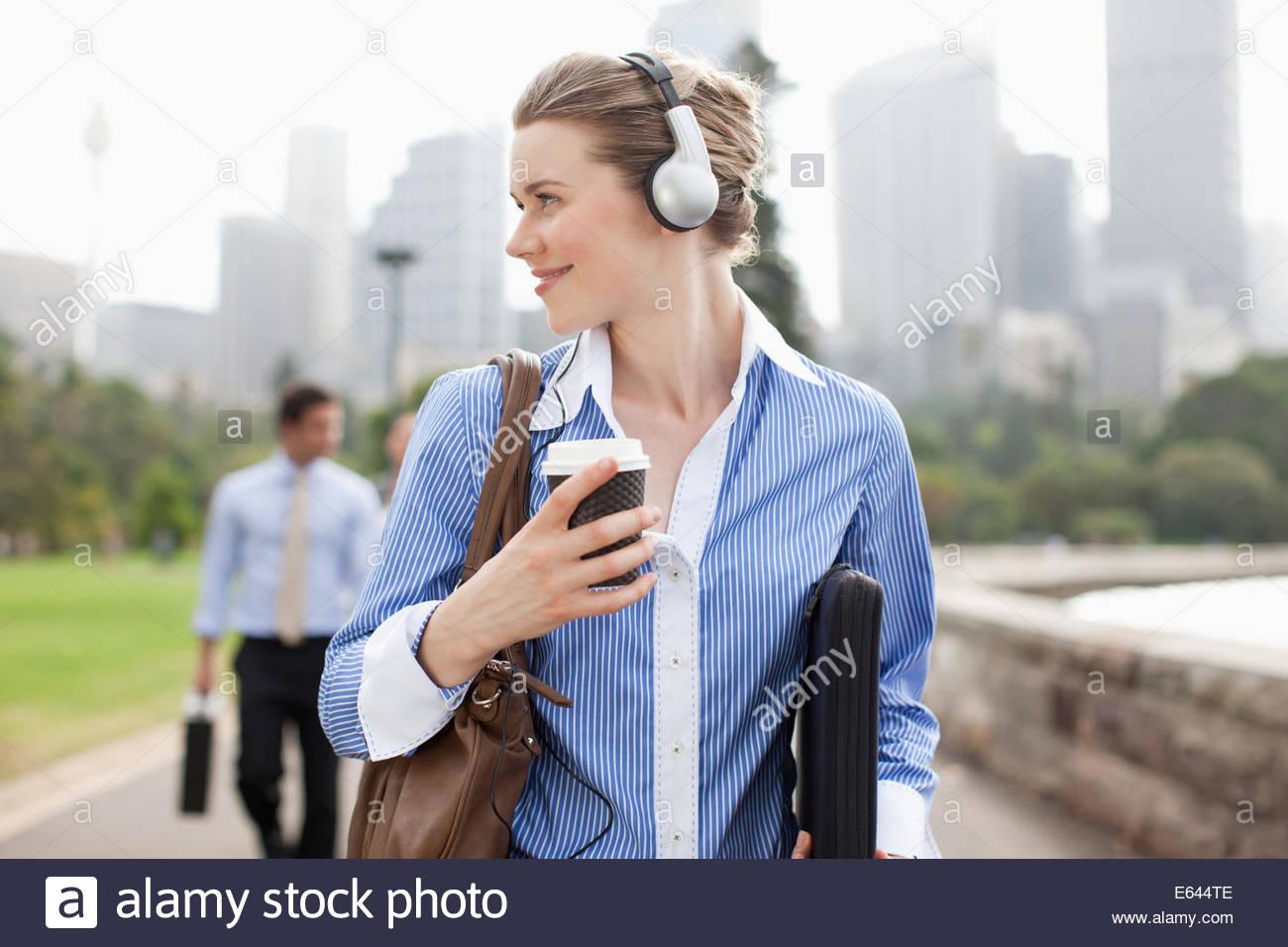 Businesswoman listening to headphones et transporter le café Photo Stock
