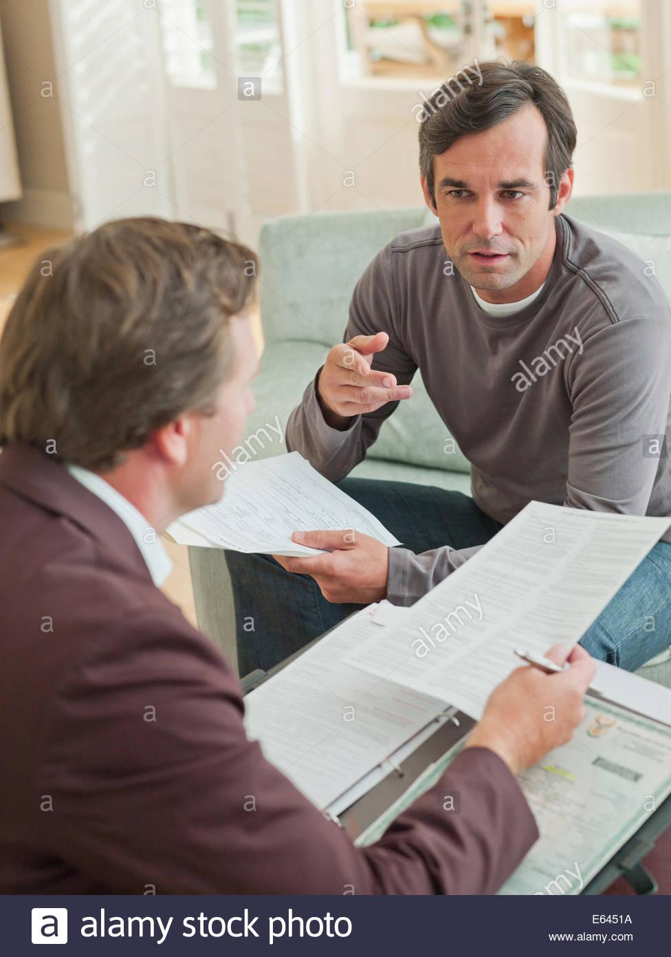 L'homme rencontre avec un conseiller financier dans la salle de séjour Photo Stock