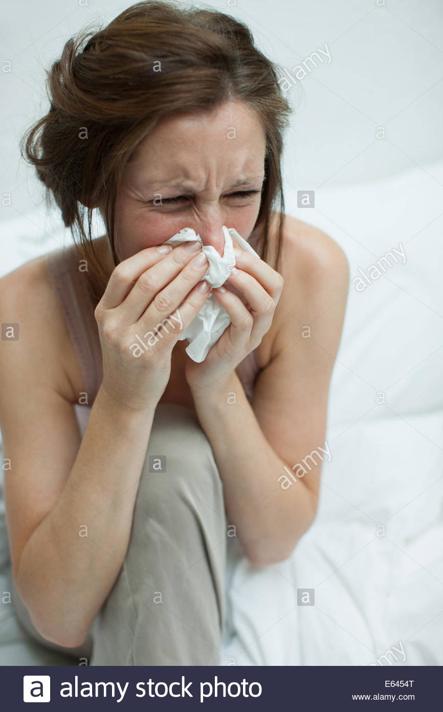 Femme malade au lit blowing nose Photo Stock